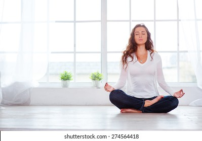Yoga at home. Keep calm. Attractive young woman sitting on lotus position on floor with eyes closed.