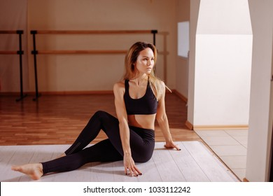 Yoga at home. Woman stretching seated spinal twist. Young slim girl makes exercise