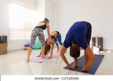 Yoga instructor adjusts student in Mysore style ashtanga class. Female teacher with young yogis in bright studio. Man in padahastasana, hands under feet pose. Healthy workout, exercise concepts