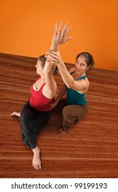 Yoga instructor assists a student stretch her shoulders