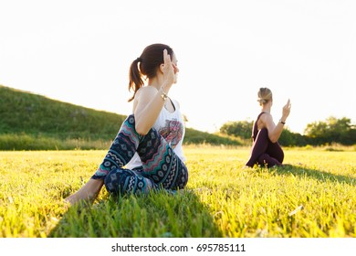 Yoga instructor doing exercise with young woman and helps beginner to make Stretching exercises. Teacher assists to make yoga pose. Healthy lifestyle at nature with green grass
