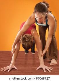 Yoga instructor helping student perform Adho Mukha Svanasana posture over orange background