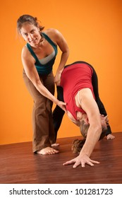 Yoga instructor helping student stretch over orange background