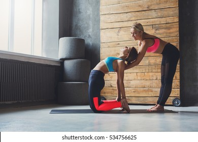 Yoga instructor helps beginner to make exercises. Teacher assists to make camel pose, ustrasana. Healthy lifestyle in fitness club. Stretching with coach