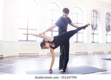 Yoga instructor helps beginner to make Stretching exercises. Teacher assists to make yoga pose. Healthy lifestyle in fitness class with windows.