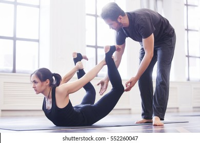 Yoga instructor helps beginner to make Stretching exercises. Teacher assists to make yoga pose. Healthy lifestyle in fitness class with windowa.