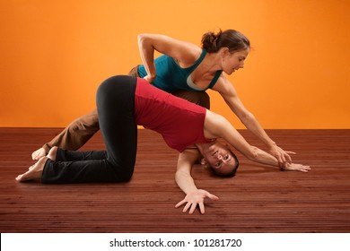 Yoga instructor helps student with stretching her shoulders