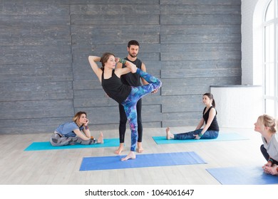 Yoga instructor helps young woman to make Pigeon exercise rigth. Teacher assists to do yoga pose or asana at seminar. Healthy lifestyle in fitness class.