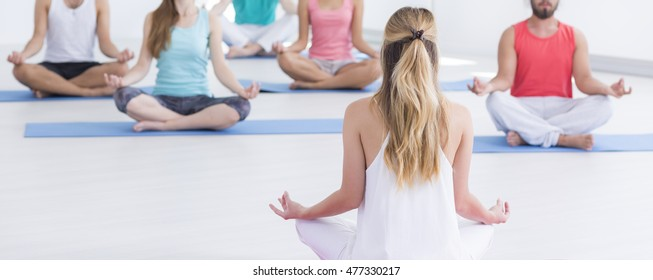 Yoga instructor meditating with group of people during classes, panorama