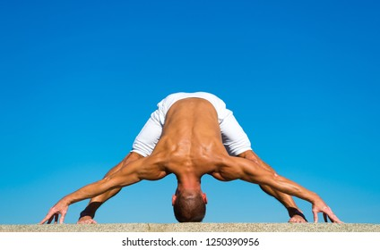 Yoga instructor with muscular body stretching. Sport and health care. Coach demonstrate yoga asana outdoors. Flexible body is his merit. Mental and physical health. Muscular man balance yoga position.