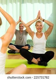 Yoga instructor showing asana to senior attenders