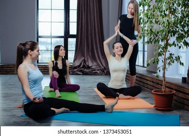 yoga instructor shows students how to do the exercise sukhasana correctly, hands namaste overhead  on yoga mat and relax breathing at studio.