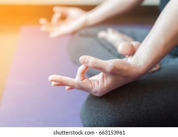 Yoga in lotus pose with woman meditating in peace relaxing in gym class under morning sun light effect