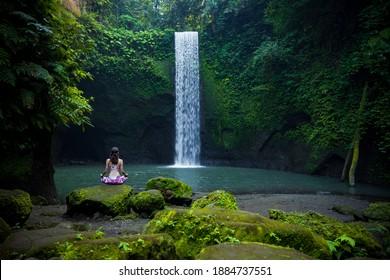 Posada de loto de yoga. Joven caucásica sentada en la piedra, meditando, practicando yoga, pranayama en la cascada. Manos en gyan mudra. Retiro de yoga. Ver desde atrás. Cascada de agua Tibumana, Bali, Indonesia