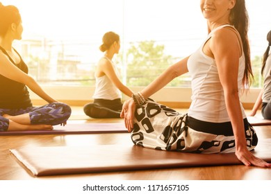 Yoga master demonstrate a yoga pose to student in group exercise with multi ethnic people