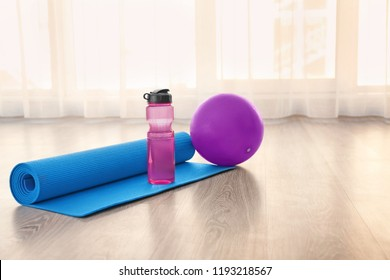 Yoga mat with bottle of water and ball on floor indoors