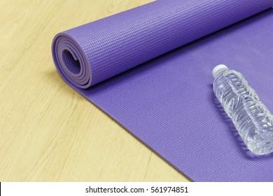 Yoga mat and drinking water bottle on wooden floor background.