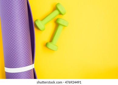 Yoga mat and dumbbells over yellow background, top view. Sport concept