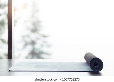 Yoga mat on the floor near big window with beautiful landscape with winter trees and mountains