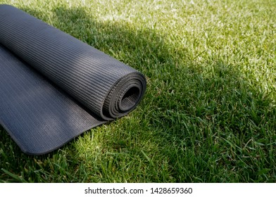 Yoga mat on a grass background. Equipment for yoga. Concept healthy lifestyle. Lots of copyspace