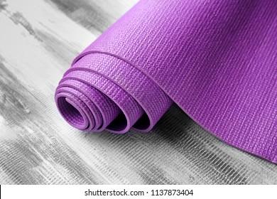 Yoga mat on wooden background, closeup