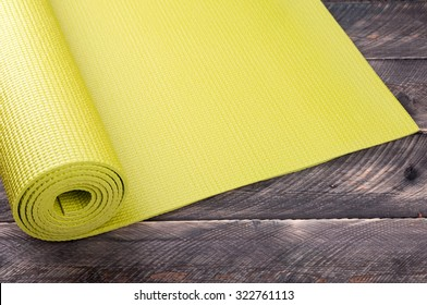 Yoga mat on a wooden background. Equipment for yoga. Concept  healthy lifestyle. Lots of copyspace. Selective focus