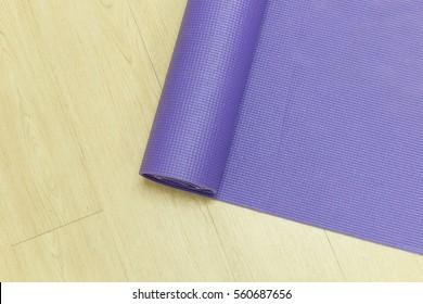 Yoga mat on wooden floor background.Exercise equipment.