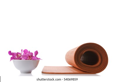 yoga mat and orchid in bowl