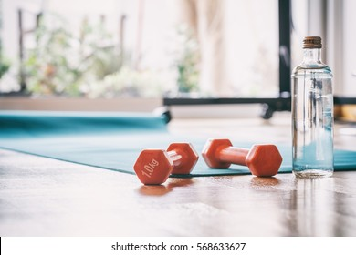 Yoga mat and a pair of weights dumbbells on wooden floor