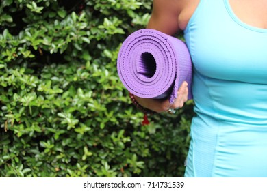 yoga mat roll holding arm background copy space under woman wearing vest tank spandex