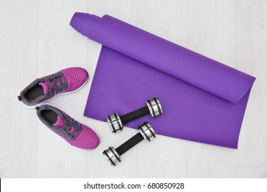 Yoga mat, sneakers and dumbbells on wooden background