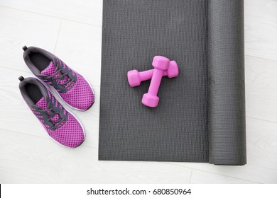 Yoga mat, sneakers and dumbbells on light background