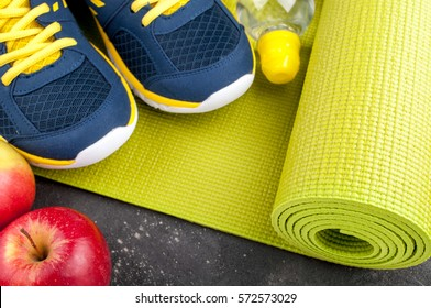 Yoga mat, sport shoes, apples, bottle of water on dark background. Concept healthy lifestyle, healthy eating, sport and diet. Sport equipment. Copy space