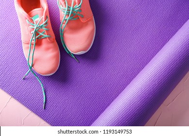Yoga mat and sport shoes in color background