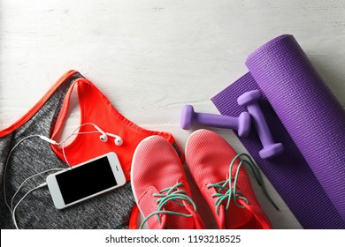 Yoga mat, sportswear, phone and equipment on white wooden background