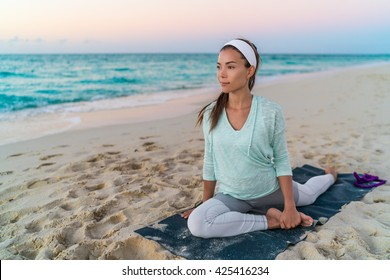 Yoga mat woman stretching hip, hamstring muscles and groin area, leg muscles with pigeon pose stretch. Fit Asian fitness athlete girl exercising sports stretches in activewear on beach at sunset.