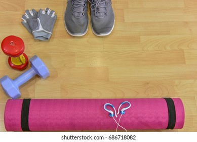 Yoga mat,Running shoes ,dumbells and headset lay down on the floor . It is Essential things for morning routine work out to keep you stay fit and healthy .