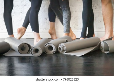 Yoga mats in a roll. Rubber carpets for individual hygiene, soft surface to perform fitness exercises, essential piece of sport gear from nonslip material. Club floor and legs at background. Close up