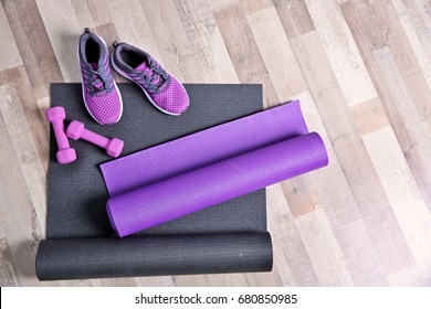 Yoga mats, sneakers and dumbbells on wooden floor
