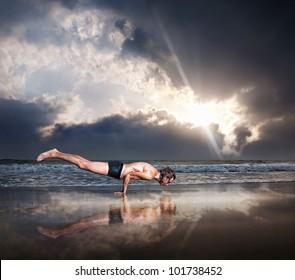 Yoga Mayurasana peacock handstand balancing pose by fit man on the beach near the ocean at dramatic sunset sky