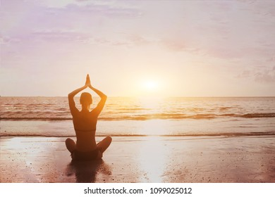 Yoga and meditation background silhouette of beautiful woman practicing breath exercises on the sea beach. Body mind and spirit, mindfulness concept. Enlightenment and healthy lifestyle