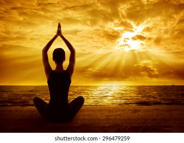 Yoga Meditation Concept, Woman Silhouette Meditating in Healthy Pose  on Beach, Back View in Sun Light Rays