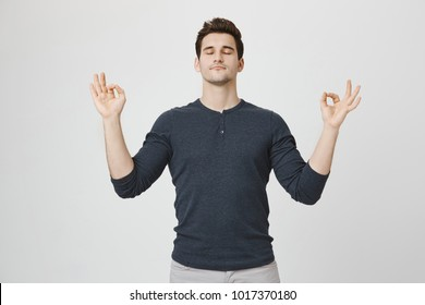 Yoga and meditation. Handsome dark-haired man with stubble keeping eyes closed while meditating, feeling relaxed, calm, peaceful after hard working day at office, holding hands in mudra sign.