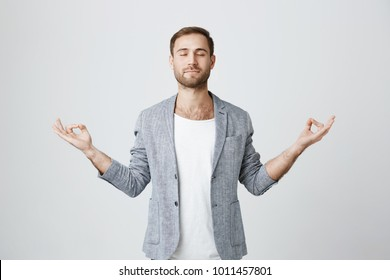 Yoga and meditation. Handsome man with beard dressed in jacket keeping eyes closed while meditating, feeling relaxed, calm, peaceful after hard working day at office, holding hands in mudra sign.