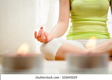 Yoga meditation at home. Relax concept with unrecognizable spiritual young woman sitting in front of candles. Caucasian concentrating model. Copyspace.