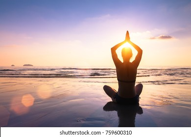Yoga and meditation on the calm peaceful beach at sunset, fit young woman