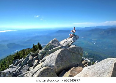 Yoga meditation on mountain top with scenic views. Mount Pilchuck. Cascade Mountains. Seattle. Washington. United States.