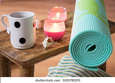 Yoga or meditation practice still life with tea, pillows, candles, and natural shells. Yoga mat and accessories for relaxation. Mindful studio at home to escape daily stress.