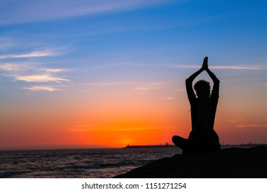 Yoga meditation woman silhouette on the ocean during amazing sunset.