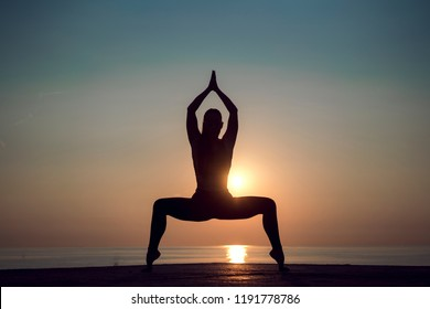 Yoga meditation woman silhouette on the ocean during amazing sunset. Woman doing stretching pilates outdoors to be healthy and live longer. Relaxing after a hard day and training. Healthy lifestyle.